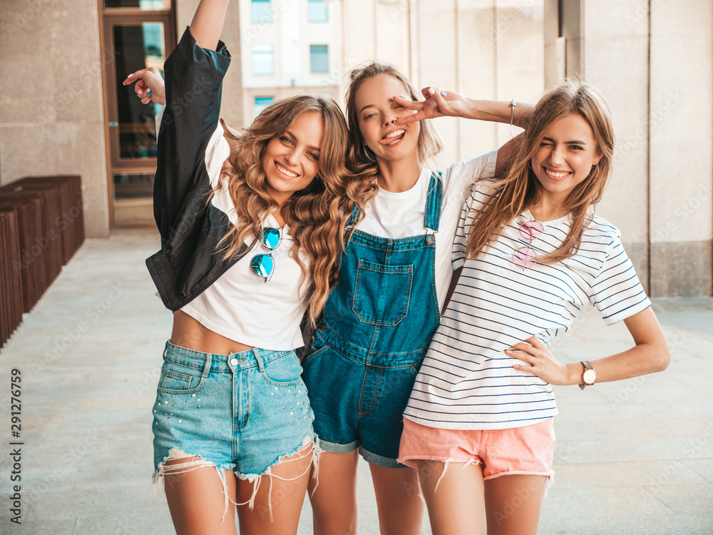 Fototapeta Portrait of three young beautiful smiling hipster girls in trendy summer clothes. Sexy carefree women posing on the street background.Positive models having fun.They raise hands