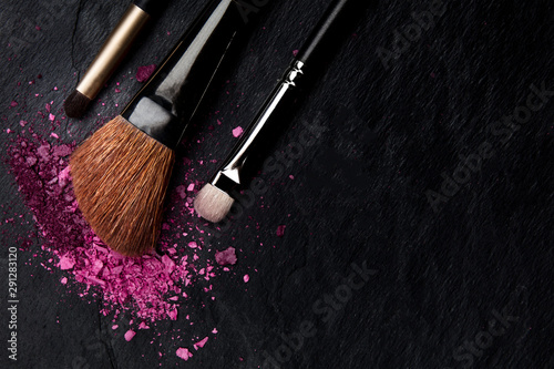 Obraz Make-up brushes with crushed cosmetics, shot from above on a black background with copyspace, a beauty design template for a makeup banner - fototapety do salonu