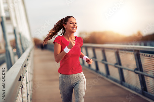 Foto Beautiful woman running over bridge