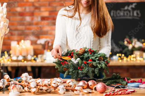 Professional florist studio. Cropped shot of lady decorating green fir tree wreath with orange slice.
