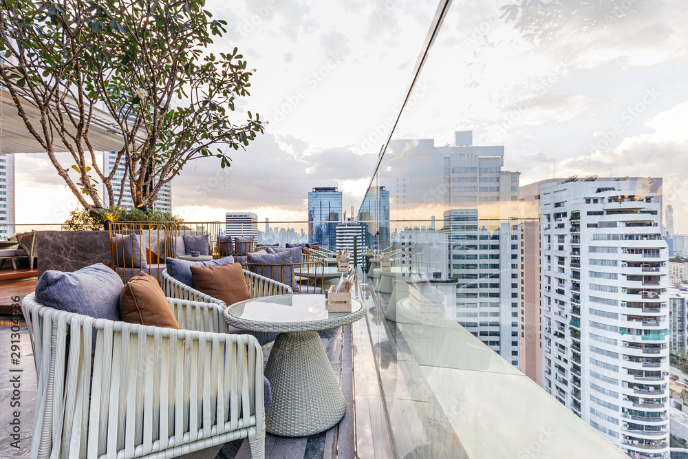 Fototapeta Outdoor rooftop bar with outdoor sofa sets in the evening. This space can take a view of modern buildings in Bangkok.