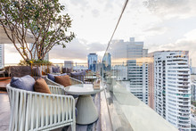 Outdoor Rooftop Bar With Outdoor Sofa Sets In The Evening. This Space Can Take A View Of Modern Buildings In Bangkok.