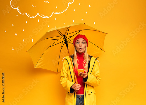 Fotografía Girl with smartphone and umbrella on yellow background surprised for the weather