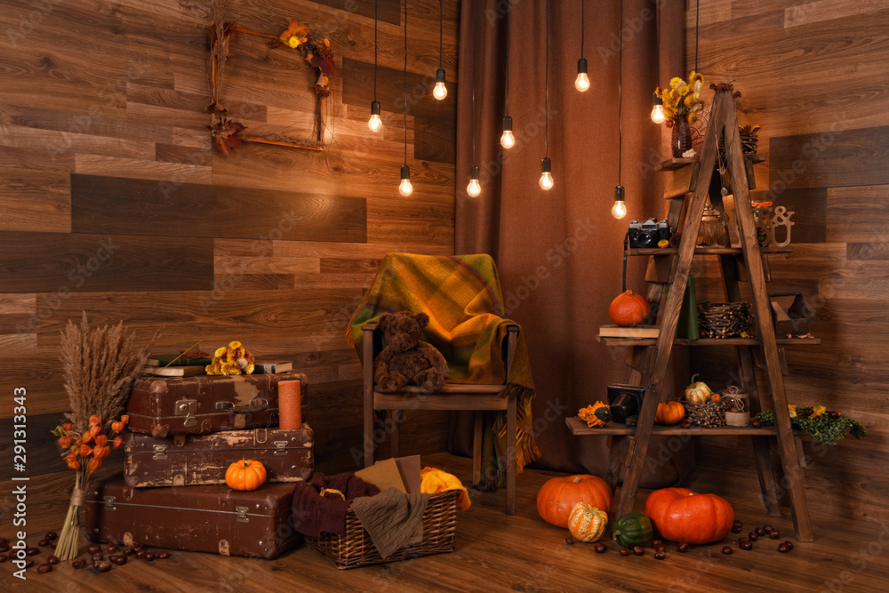 Fototapeta Beautiful vintage autumn composition with pumpkins, teddy bear, magic lights, cozy plaid and old suitcases. Fall season. Thanksgiving and Halloween concept.