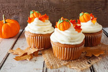 Fall Pumpkin Spice Cupcakes With Creamy Frosting And Autumn Toppings. Close Up Against A Rustic Wood Background.