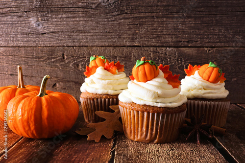 Obraz na plátně  Fall pumpkin spice cupcakes with creamy frosting and autumn toppings