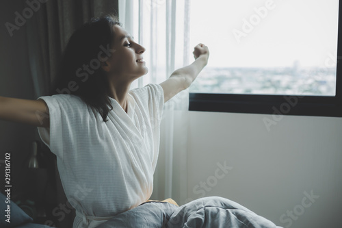 Obraz Attractive beautiful woman wakes up in morning and stretching body by hands raise. Charming beautiful young woman feels relaxing, happiness and gets fresh air. She looks at beautiful view, smile face - fototapety do salonu