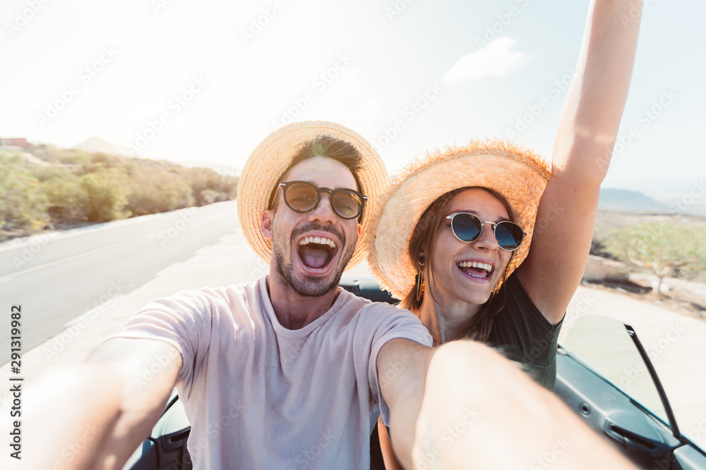 Fototapety, obrazy: Happy couple in love taking a selfie when road trip in a convertible car