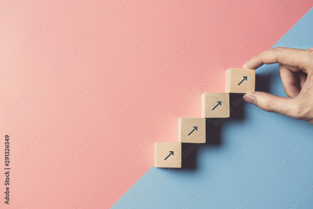 Fototapety, obrazy: Business concept growth success process, Close up man hand arranging wood block stacking as step stair on paper blue and pink background, copy space.
