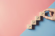 Leinwanddruck Bild - Business concept growth success process, Close up man hand arranging wood block stacking as step stair on paper blue and pink background, copy space.