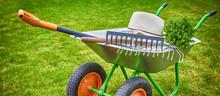 Wheelbarrow With Gardening Tools In The Garden.banner