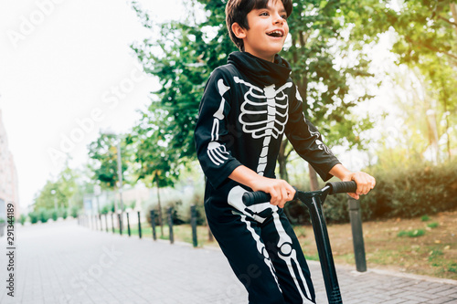 Valokuva  Boy in skeleton costume standing in street with scooter