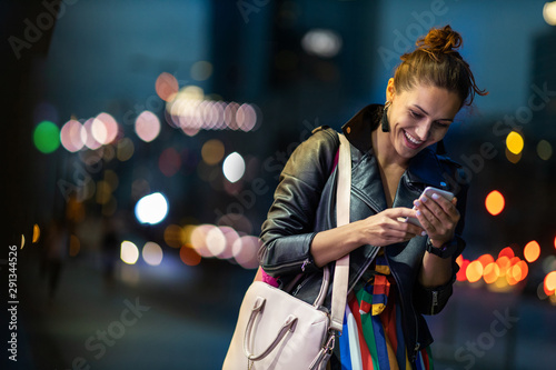 Photo Stands Music store Young woman with smartphone at night in a urban city area