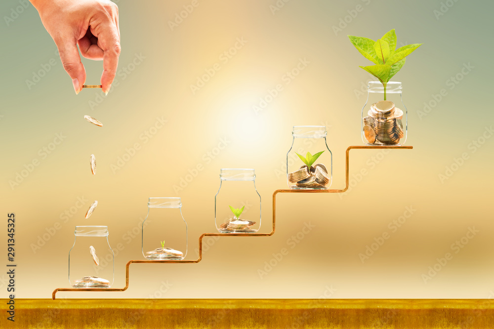 Fototapety, obrazy: Investor hand hold and drop a gold coin in the five bottle and plant growing on golden steps on sunlight background, Business investment and saving money concept.