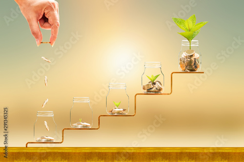 Fototapeta Investor hand hold and drop a gold coin in the five bottle and plant growing on golden steps on sunlight background, Business investment and saving money concept. obraz