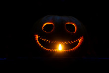 Funny Pumpkin Head Is Illuminated By A Candle In The Dark