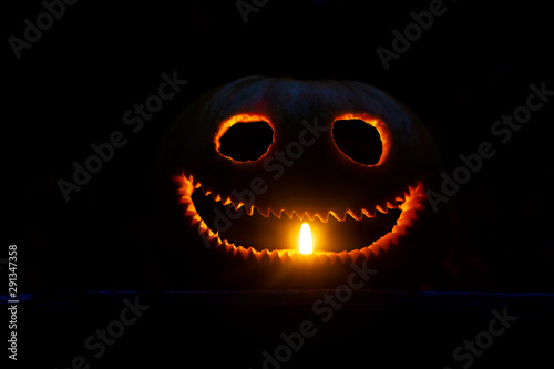 funny pumpkin head is illuminated by a candle in the dark Tapéta, Fotótapéta