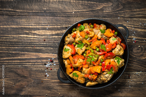 Photo  Chicken Stir fry with vegetables on wooden table.