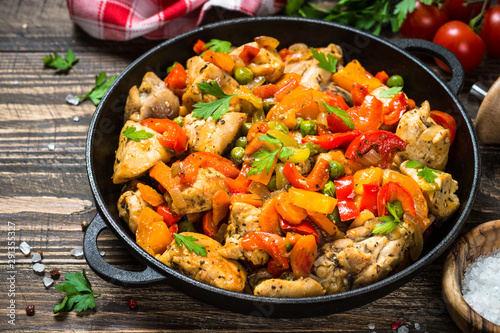 Chicken Stir fry with vegetables on wooden table. Canvas Print