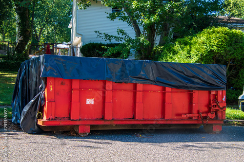 Canvas Print Red dumpster with black plastic liner on a asphalt street near the side of a hou