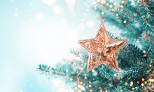 Christmas Fir Tree Branches With Golden Star Decoration  On Blurred Blue Background. Christmas And Winter Concept.