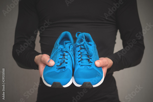 Pair of new sneakers in the sportsmen hands on gray background. Canvas Print