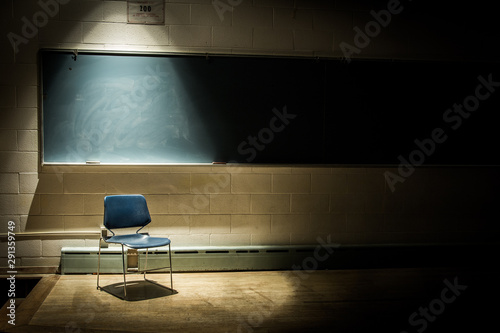 Canvas Print An Empty School Chair in a Dark, Shadowy Classroom - in Front of a Chalkboard wi