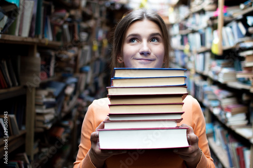 Photographie girl student holds a stack of books in the library, she searches for literature