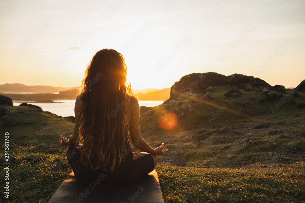 Fototapeta Woman meditating yoga alone at sunrise mountains. View from behind. Travel Lifestyle spiritual relaxation concept. Harmony with nature.