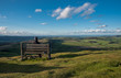 A hiker sitting on a bench taking in the views from Corndon Hill, Powys