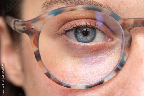 close up on young girl blue eye wearing with corrective lens glasses Wallpaper Mural