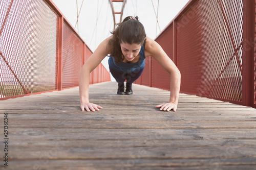 Valokuvatapetti woman training push ups on a bridge