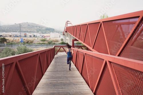 mid adult woman running on a bridge Canvas-taulu