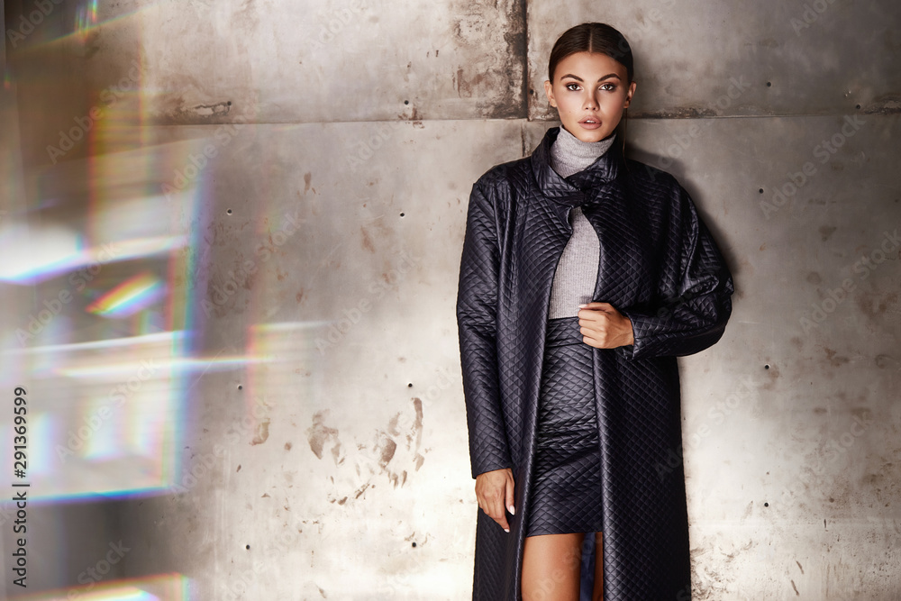 Fototapeta Beautiful young sexy woman lady stylish elegant lather skirt trench coat makeup and hair style for the evening business meeting walk date designer with accessories lather black high heels skin tan.