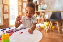 Beautiful African American Toddler Drawing Using Paper And Marker Pen Smiling At Kindergarten