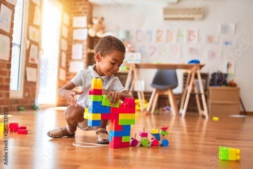 Beautiful african american toddler playing with building blocks smiling at kindergarten