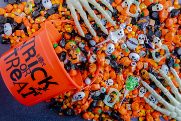 Halloween candy spilling out of orange trick or treat bucket