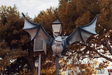 A Decorative Flying Vampire Bat On A Lamppost. Happy Halloween And Street Decoration Concept.