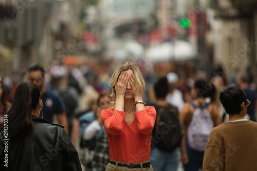 Pinturas sobre lienzo  Sad depressed woman covers his eyes with his hands surrounded by people walking in crowded street