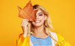 canvas print picture happy emotional girl with autumn leaves on colored yellow background