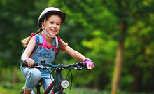 Happy Cheerful Child Girl Riding A Bike In Park In Nature.