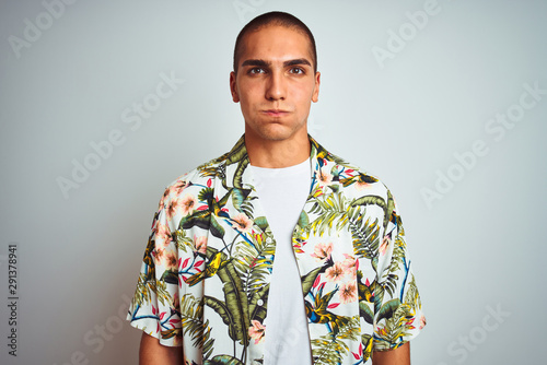 Young handsome man on holidays wearing Hawaiian shirt over white background puffing cheeks with funny face. Mouth inflated with air, crazy expression.