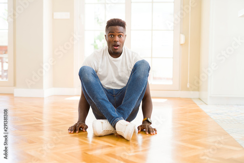 Photo Handsome african american man sitting on the floor at home afraid and shocked with surprise expression, fear and excited face