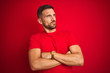canvas print picture - Young handsome man wearing casual t-shirt over red isolated background looking to the side with arms crossed convinced and confident