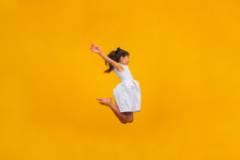 Beautiful Asian Girl Sitting On Yellow Background. Happy Little Asian Girl Smiling.