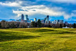 Clouds Gather over Denver Skyline in the Evening - Grassy Field in Foreground