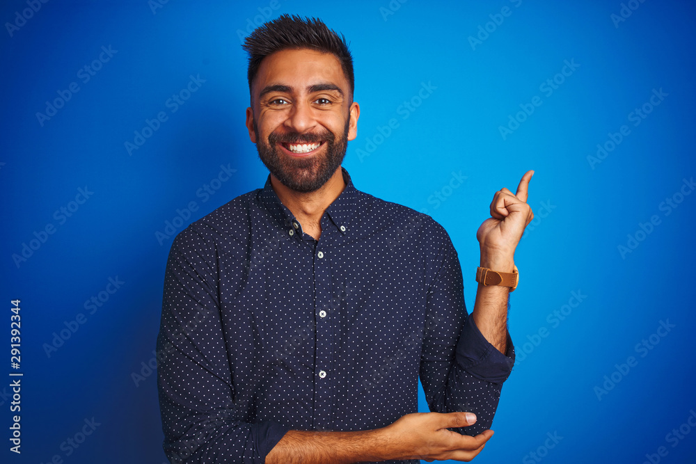 Fototapeta Young indian elegant man wearing shirt standing over isolated blue background with a big smile on face, pointing with hand and finger to the side looking at the camera.