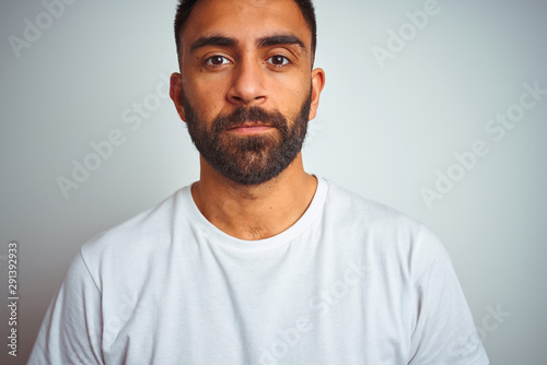 Obraz na plátně Young indian man wearing t-shirt standing over isolated white background with serious expression on face