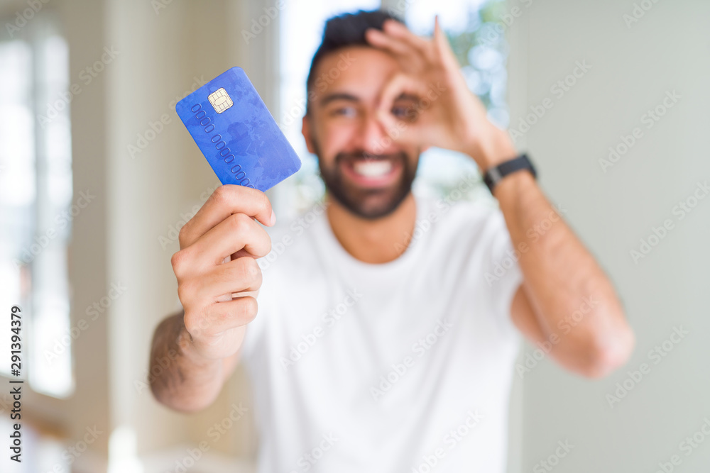 Fototapety, obrazy: Handsome hispanic man holding credit card with happy face smiling doing ok sign with hand on eye looking through fingers