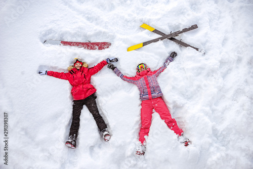Fotomural  Aerial photo of skier and snowboarder lying on snow